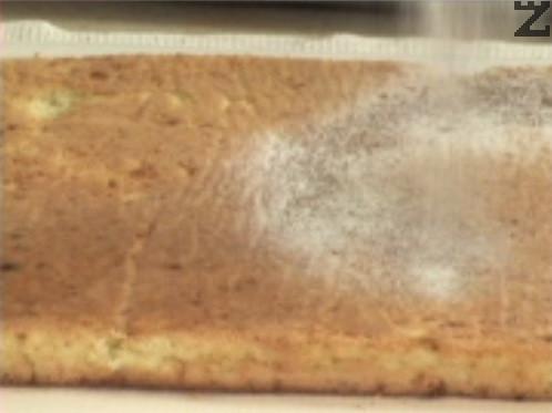 Върху плота слагаме кърпа, отгоре разстиламе хартия за печене. Върху нея пресяваме половината какао и пудра захар, поръсваме с кристална захар. Вадим платката от тавата, обръщаме я върху плота и отстраняваме хартията за печене. Отгоре поръсваме с останалото количество какао и пудра захар.