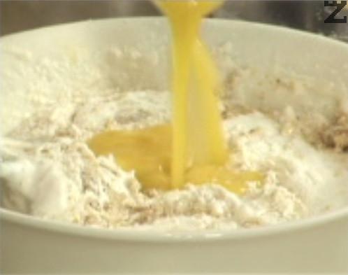 Поливаме с ванилия, добавяме и разтопено краве масло. Разбъркваме със силиконова шпатула, докато се получи еднородна смес.
