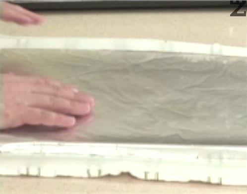 Оставяме платката да се охлади 10 мин., след което обръщаме върху кърпа и хартия за печене. Отстраняваме фолиото и внимателно навиваме на руло. Изчакваме напълно да изстине, развиваме го и нанасяме крема сирене. Изравняваме добре повърхността, отгоре поръсваме с натрошена сушена чушка.