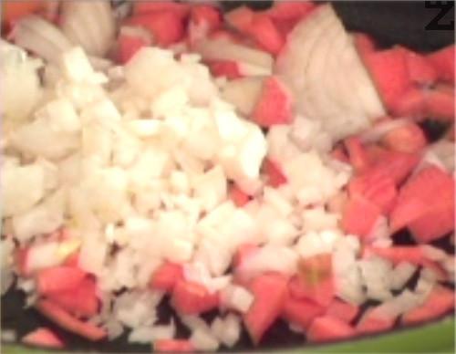 През това време задушаваме наситнен кромид лук, заедно с нарязани на кръгчета моркови за 1 мин. Режем целина и я прехвърляме към леко омекналите зеленчуци.