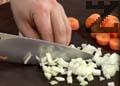 Нарязваме моркова и кромида на ситно. Загряваме половината количество масло в голяма тенджера и задушаваме нарязаните зеленчуци за 30 секунди.