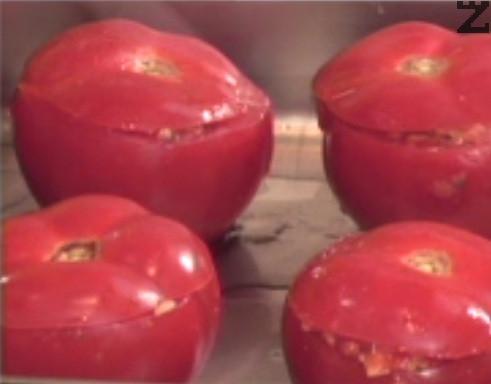 Пълним доматите с плънката, затваряме с капачета и поливаме с олио. Редим в намаслена тавичка и поставяме в средата на предварително загрята фурна. Печем на 180 градуса за 30-35 мин.