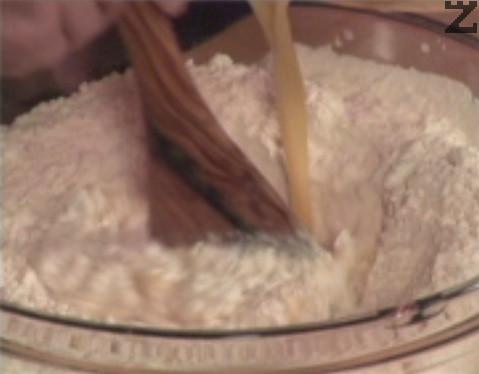 В купа пресяваме брашно, оформяме кладенче и постепенно наливаме млечно-яйчената смес.