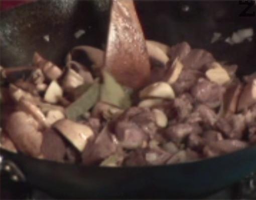 След като месото се зачерви и част от течността изври, добавяме нарязан на ситно кромид лук и филийки прясна печурка. Разбъркваме и задушаваме на по-слаб огън.