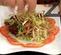 Нарязваме домат на полумесеци, аранжираме резените в кръг в чиния за сервиране. В центъра на чинията слагаме салатата. Отгоре поставяме пилешките жулиени, поливаме със соса и добавяме гъбите. Декорираме салатата с лучени кълнове и я поднасяме.