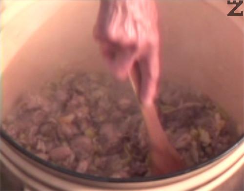Режем лук на ситно и го прехвърляме към месото. Разбъркваме, запържваме за кратко и добавяме нарязани на ситно чушки. Посоляваме и задушаваме зеленчуците.