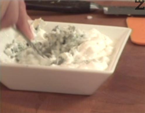 В купичка смесваме сирене и сметана, разбъркваме и поръсваме със сол и бял пипер.