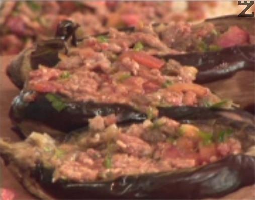 Пълним патладжаните с приготвената смес, като притискаме добре. Белим домат, нарязваме го на четвъртинки и махаме сърцевината му. Покриваме пълнените патладжани с резен домат и ивичка зелена чушка.