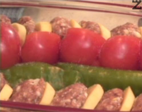 Така оформяме две редички, като между тях /в средата на тавата/ подреждаме нарязаните на едро домати и зелени чушки. Посоляваме и поливаме със зехтин, поръсваме с наситнен магданоз.