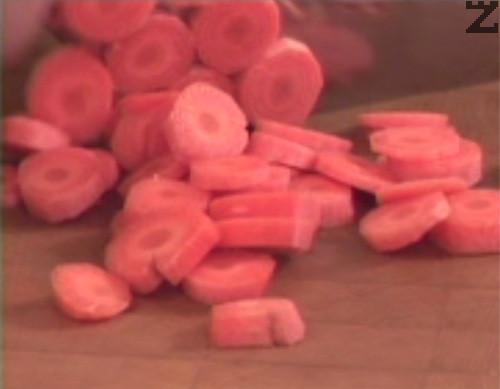 През това време режем на колелца моркови, а чесън - на едро и ги прехвърляме към останалите продукти.