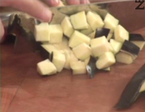 Нарязваме на малки кубчета патладжан и го поставяме в тиган. Запържваме в сгорещен зехтин за няколко минути, заедно с нарязаните на ситно скилидки чесън.
