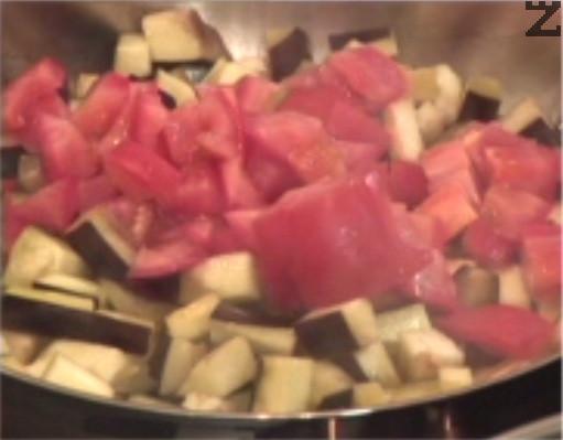 След като продуктите омекнат, прибавяме нарязани на кубчета домати. Разбъркваме и пържим за кратко.