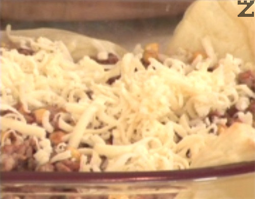 Прехвърляме плънката върху изпечения лист бутер тесто. Отгоре поръсваме с половината от настърган на едро ренде кашкавал.
