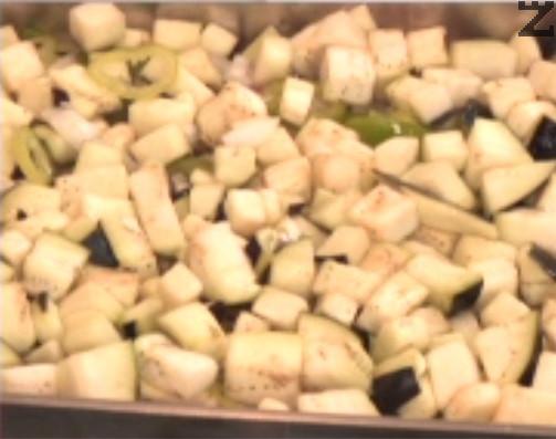 Отгоре покриваме с нарязан на по-едри парченца кромид лук, добавяме и нарязани на колелца или ивички чушки. Отцеждаме патладжана, измиваме го добре със студена вода и го прехвърляме при останалите продукти. Притискаме добре и поливаме с олио.