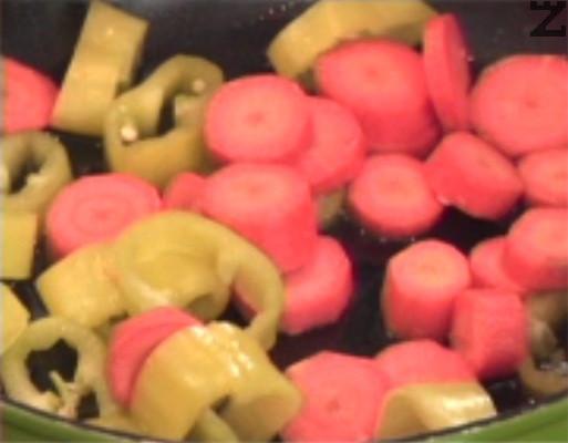 През това време нарязваме зеленчуци на едро и ги запържваме за кратко в сгорещено олио.