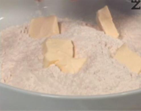 Приготвяме тестото. Нарязваме студено краве масло на парченца, които поставяме в купа, заедно с брашно. Месим с ръце и претриваме с пръсти, докато се получи смес, подобна на пясък. Поръсваме със сол, наливаме постепенно 100 мл студена вода.
