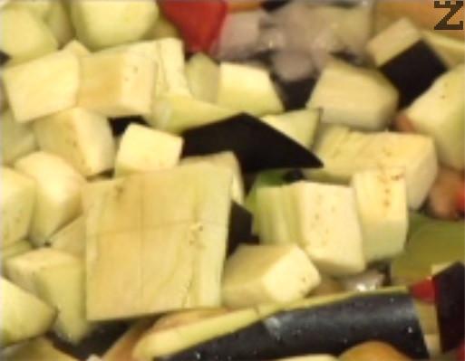 Измиваме патладжана, отцеждаме го добре и го нарязваме на кубчета. Прехвърляме към останалите зеленчуци. Задушаваме за 10 мин. на умерена степен на котлона, в самия край добавяме по едро-нарязани скилидки чесън.