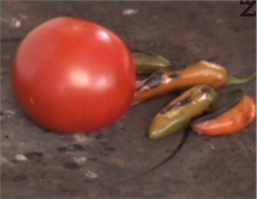 На плочата на котлон се изпичат домати и люти чушки.