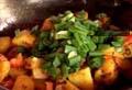 Добавяме куркума, картофи и нарязан пресен лук. Задушаваме в масло няколко минути и сервираме.