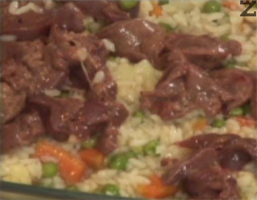 Намасляваме тавичка за печене, отгоре слагаме половината ориз. Разпределяме пилешките дробчета и воденичките, покриваме с останалия ориз.