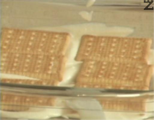 Нанасяме фин пласт от крема на дъното на тавичка. Покриваме с ред бели бисквити, потопени в затоплено мляко.