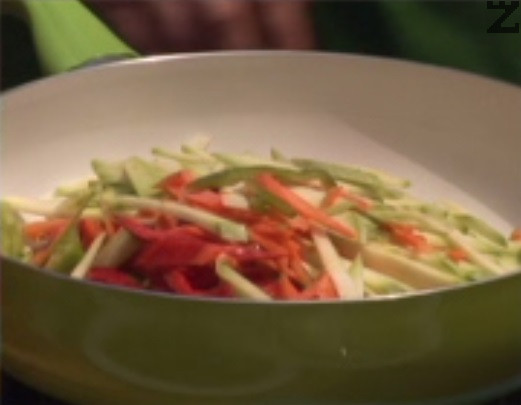 В зехтин запържваме нарязаните на ивички моркови и чушки, посоляваме и поръсваме с черен пипер на вкус. След 1-2 мин. добавяме и останалите зеленчуци.