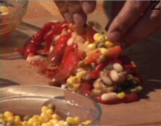 Добавяме сварен боб, покриваме с ивички камби. Слагаме моркови, царевица и грах, поливаме с 2 с.л. от олиото, в което сме пържили рибата.