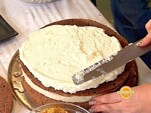 Поставя се втора платка, сиропира се с един черпак от сиропа и се нанася 1/3 от сметановия крем. Отново се поръсва с една-две шепи от ореховия крокан