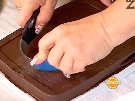 С дъгообразен нож се оформят шоколадови цилиндри.