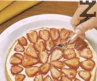 Върху сметаната се редят филийки от подсладените ягоди.
