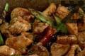 Прибавяме нарязаната зелена чушка и разбъркваме. Слагаме сос от стриди, наливаме вода и връщаме запърженото кашу в уока. Сервираме ястието в подходяща чиния, декорирано със стрита суха чушка по желание.