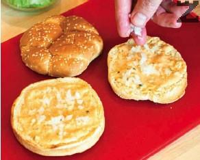 Основата на всяка от запечените питки се намазва със сос, слага се малко лук.