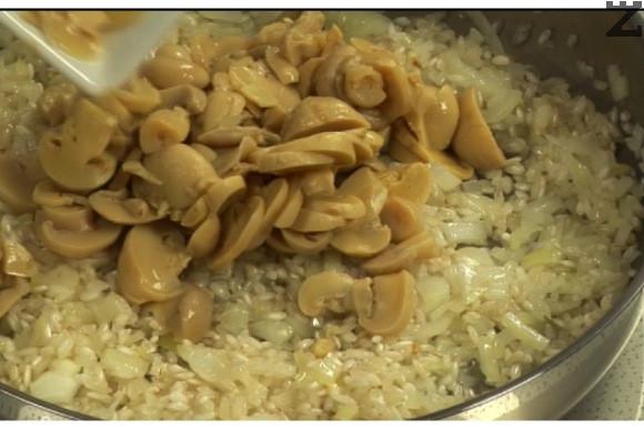Лукът се задушава в олиото за 30 секунди, прибавят се нарязани на дребно гъби и се пържат за минута. Слага се и оризът.
