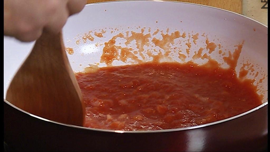 Приготвя се доматения сос като се нарязва лука на ситно, и запържва в касерола с загрят зехтин за 30 секунди, прибавят се пасирани домати, сол,чесън, захар и риган. Вари се 2-3 минути.