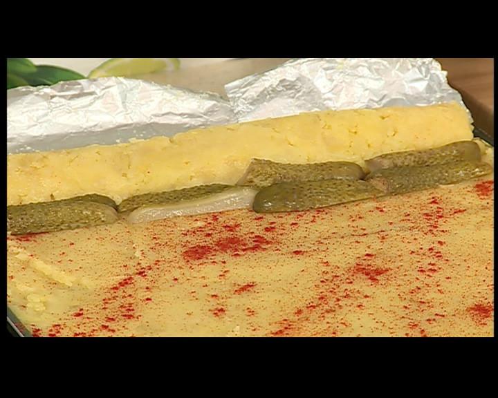 В едната част се слага нарязано на пръчици филе.НАвива се част от рулото, и се слгата кисели краставички отново се завива и се редят маслини,така се повтаря процеса докато се навие руло.