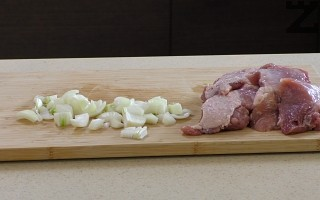 През това време се нарязва на едро лук. След като месото побелее, се слага лукът. Разбърква се и посолява. Слага се капак на слаб огън под капак месото се задушава 10 минути.