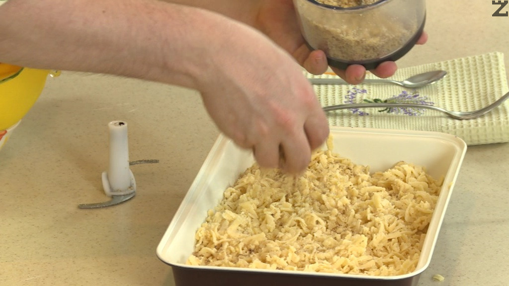 Ореховите ядки се мелят на дребно и слагат върху сладкиша.