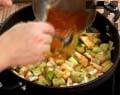 Наливаме олио, поръсваме с червен пипер и добавяме доматено пюре. Прехвърляме сместа в съд за печене и добавяме нарязан праз лук. Наливаме топла вода, поръсваме със сол и захар. Запичаме ястието 10 мин. във фурна, загрята на 180-200 градуса.