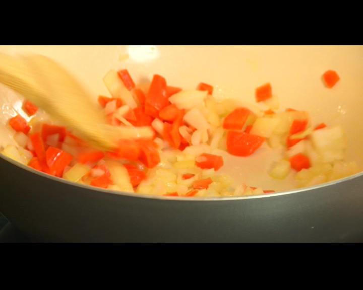 Ориза се измива с вода и залива с 500 мл студена вода за да престои накиснат за 20 минути В тиган се загрява олио и се пържи ситно нарязан лук за минута заедно с моркова нарязан на малки кубчета.