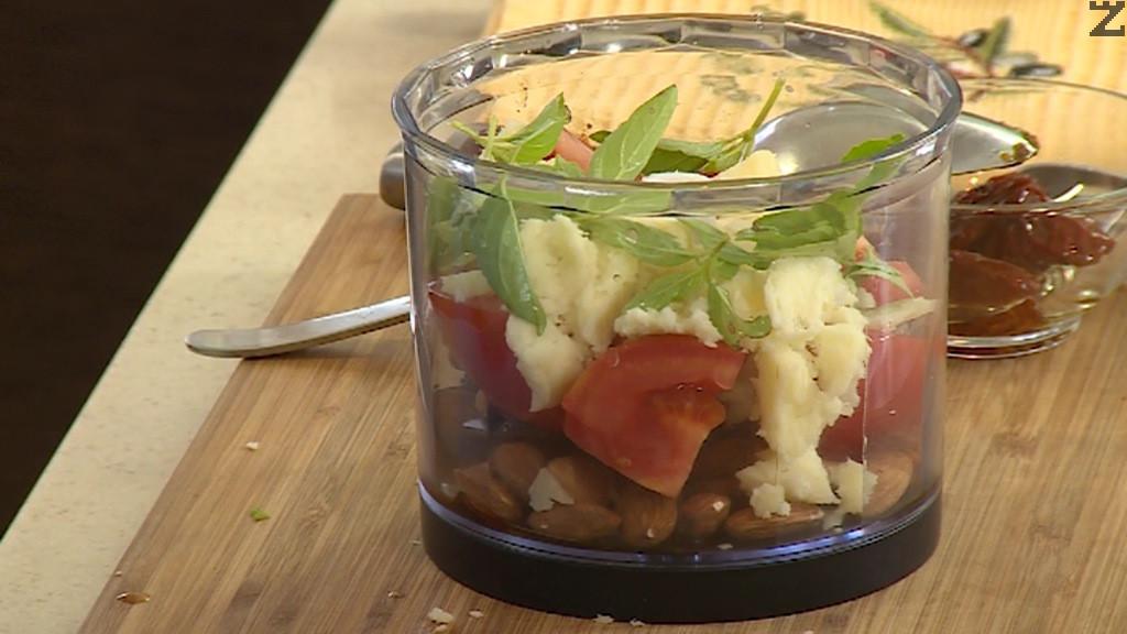 Прави се песто като в чопър се слагат бадеми, босилек,, сушени мариновани домати, чесън, настърган кашкавал ( сирене ) и дребно нарязан домат.