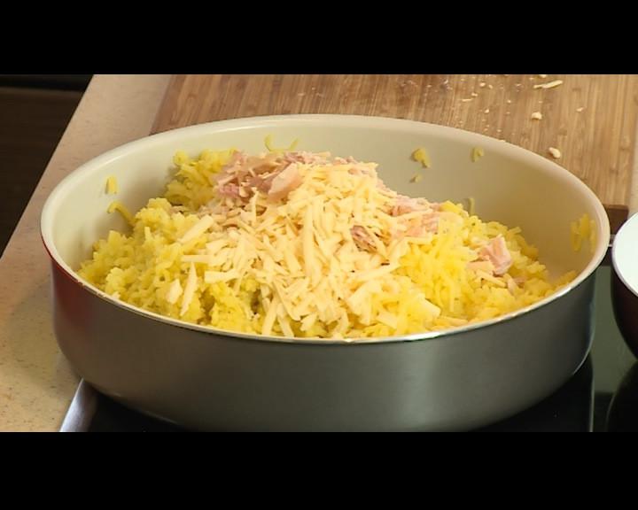 Кашкавала се настъргва върху картофите, а бекона се нарязва на малки кубчета.