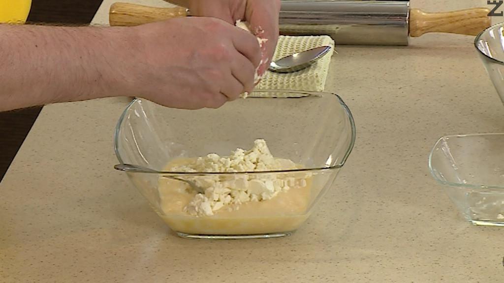 Яйцата се разбиват за кратко с вилица и се добавя киселото мляко, натрошено сирене и хубаво се разбърква.