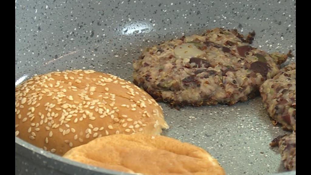 Питката за хамбургер се реже на две, всяка половинка се запича в тигана при бургерите до златисто.