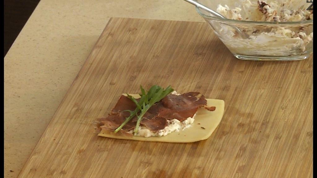 Върху филия сирене Ементал се нанася пласт от крема сирене с домат, фини ивици пастърма и листа рукула.