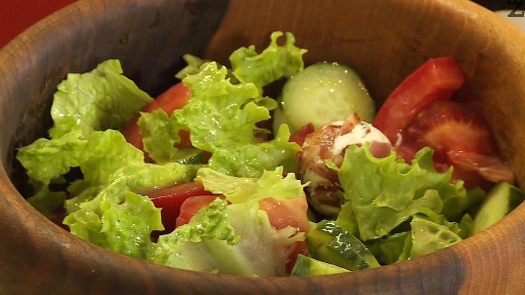 В купа се накъсва зелена салата, добавя се нарязана колелца краставица и едро нарязан домат.