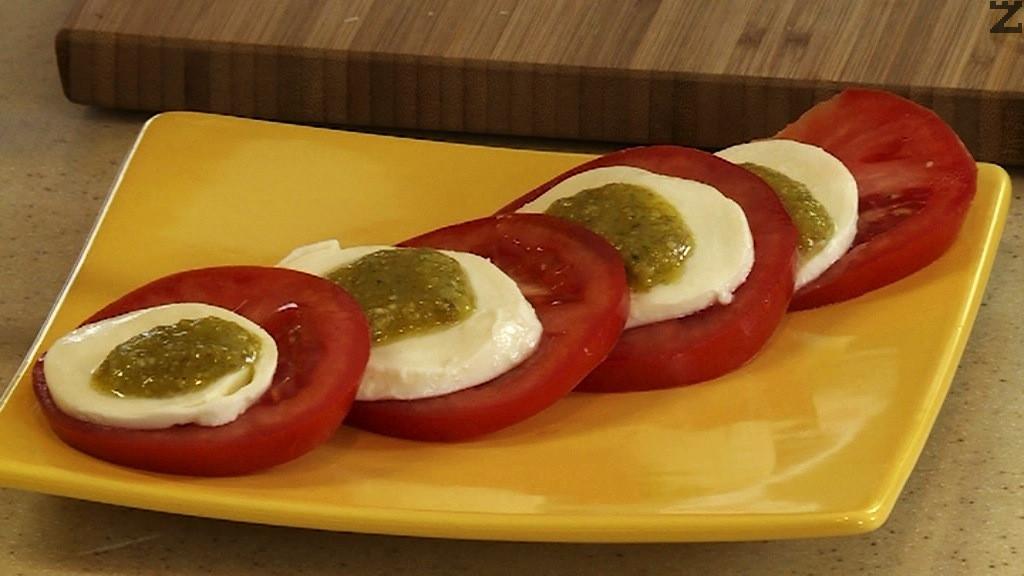 В чиния се слага резен домат леко се покрива с моцарела върху нея се слага отново домат, покрива се с моцарела и така общо шест пъти.
