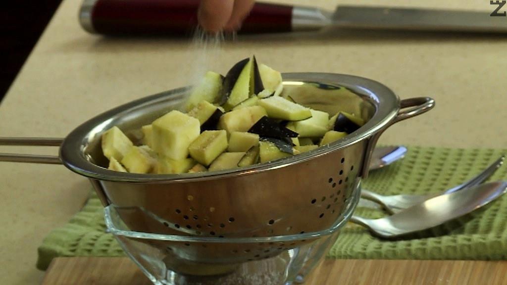 Патладжана се бели на ивички, и реже на малки кубчета. Осолява се и оставя да се махне горчивия сок за 15-20 минути. Изплаква се и подсушава.
