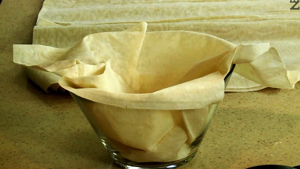 В купичка с вместимост 300-400 мл, се слага лист кора за баница.