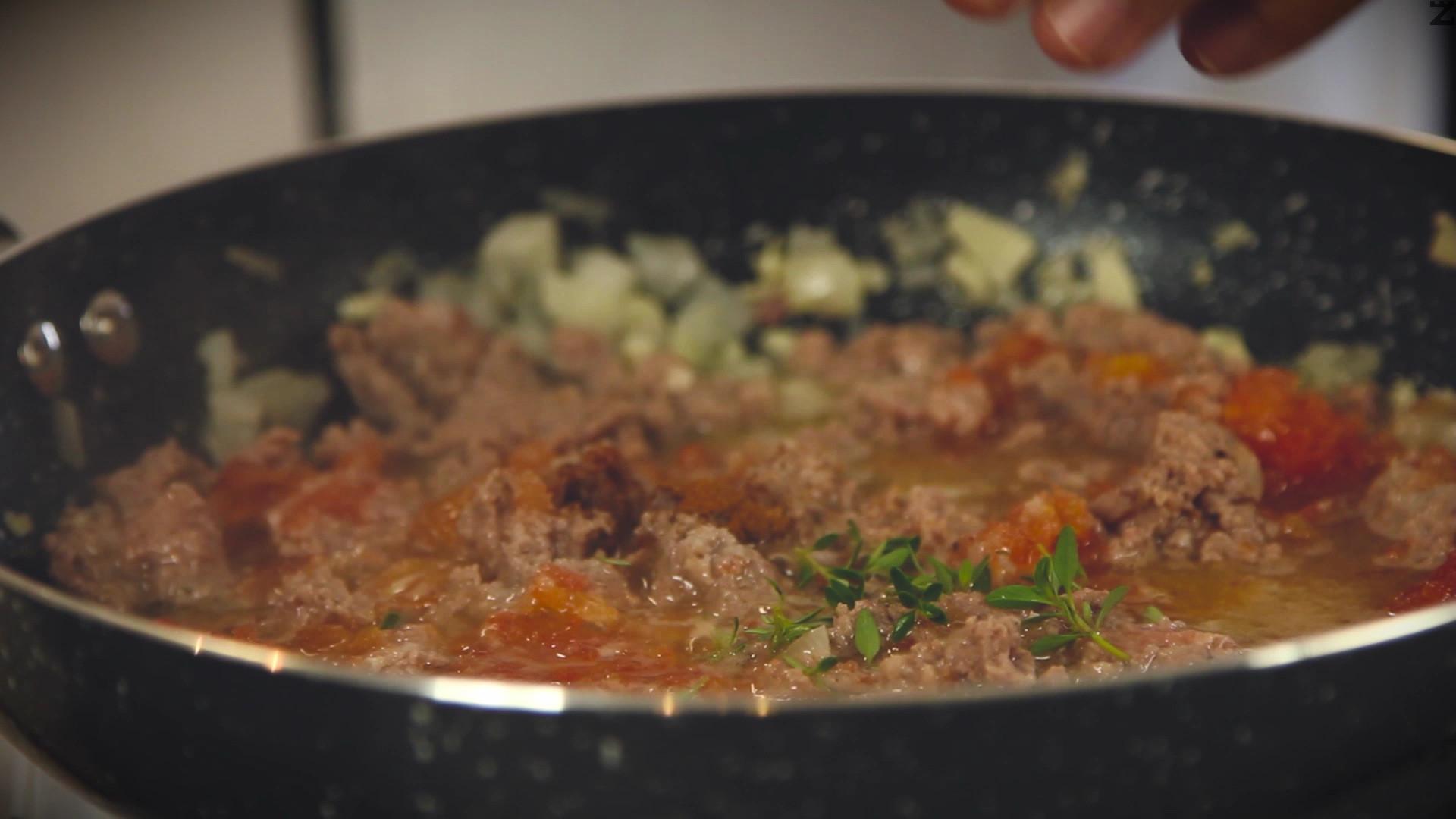 Лукът и чесънът се нарязват наситно и запържват за минута в 3 с.л. зехтин. Добавя се каймата и пържи за минута като се бърка за да стане на трохи. Посолява се с 1 ч.л. сол, подправя се с канела и риган и се слагат доматите. Задушава се под капак на слаб огън за 15 минути.