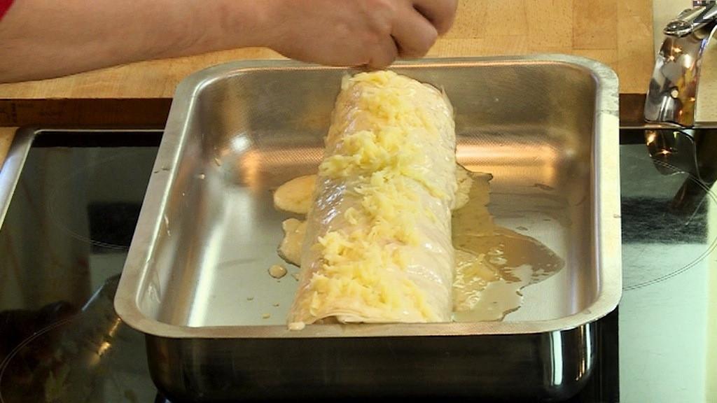 В купичка се разбива едно яйце с кисело мляко. С тях се намазва рулото и се поръсва с останалия настърган кашкавал. Пицата се пече на 180С в предварително затоплена фурна за 30 минути.